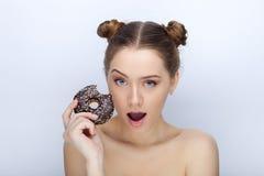 Porträt einer jungen Frau mit lustiger Frisur und bloßer Schultertat der Affe gegen weißen Studiohintergrund mit Schokoladendonut Lizenzfreies Stockfoto