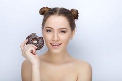 Porträt einer jungen Frau mit lustiger Frisur und bloßer Schultertat der Affe gegen weißen Studiohintergrund mit Schokoladendonut Lizenzfreie Stockfotografie