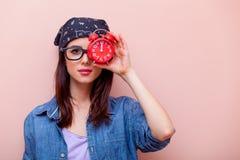 Porträt einer jungen Frau mit Wecker Stockbild