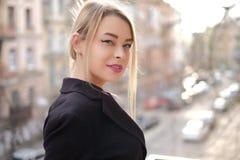Porträt einer jungen Frau in einer schwarzen Anzugsnahaufnahme gegen einen Hintergrund einer undeutlichen Stadt in den Strahlen d Stockbilder