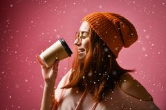 Porträt einer jungen Frau in trinkendem Kaffee des Winterstoffes lizenzfreie stockfotografie