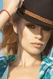 Porträt einer jungen herrlichen blonden Frau mit dem provozierenden Make-up, das schwarzen geglaubten Hut trägt Lizenzfreie Stockfotografie