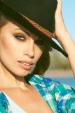 Porträt einer jungen herrlichen blonden Frau mit dem provozierenden Make-up, das schwarzen geglaubten Hut trägt Stockbild
