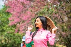 Porträt einer jungen Jugendlichen, die ein Rosa in einem Park trägt lizenzfreie stockfotografie