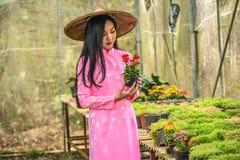 Porträt einer jungen Jugendlichen, die ein Rosa in einem Park trägt lizenzfreies stockfoto