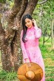 Porträt einer jungen Jugendlichen, die ein Rosa in einem Park trägt lizenzfreie stockfotos