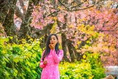 Porträt einer jungen Jugendlichen, die ein Rosa in einem Park trägt stockbilder