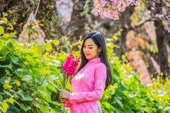 Porträt einer jungen Jugendlichen, die ein Rosa in einem Park trägt lizenzfreie stockbilder
