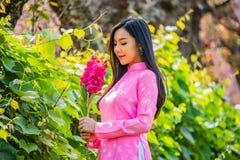 Porträt einer jungen Jugendlichen, die ein Rosa in einem Park trägt stockfoto