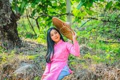 Porträt einer jungen Jugendlichen, die ein Rosa in einem Park trägt stockbild