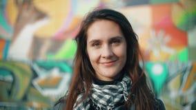 Porträt einer jungen lächelnden Frau in den Strahlen der untergehenden Sonne auf einem bunten Hintergrund Nahaufnahme 4K Lizenzfreie Stockbilder