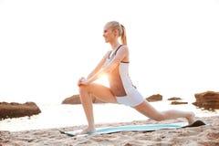 Porträt einer jungen lächelnden Frau, die Beine auf Strand ausdehnt Lizenzfreie Stockbilder