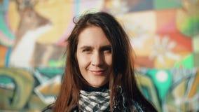 Porträt einer jungen lächelnden Frau genießen die rayss der untergehenden Sonne auf einem bunten Hintergrund Nahaufnahme 4K Lizenzfreie Stockfotos