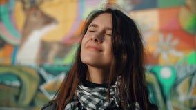 Porträt einer jungen lächelnden Frau genießen die rayss der untergehenden Sonne auf einem bunten Hintergrund Nahaufnahme 4K Lizenzfreies Stockfoto