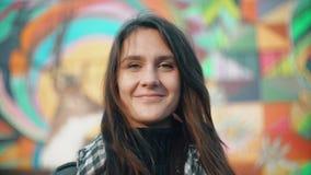 Porträt einer jungen lächelnden Frau rüttelt den Kopf und blinzelt auf einem bunten Hintergrund Nahaufnahme 4K Lizenzfreie Stockbilder