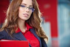Porträt einer jungen lächelnden Geschäftsfrau, in einem Büroen lizenzfreie stockfotos