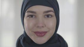Porträt einer jungen lächelnden Ostfrau in der modernen moslemischen Kleidung und schönen schwarzen im Kopfschmuckabschluß oben j stock video footage
