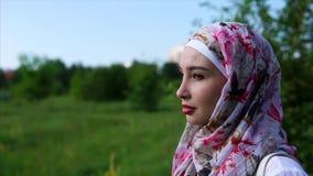 Porträt einer jungen moslemischen Frau, die ein hijab trägt, das Einsamkeit im Park genießt stock video