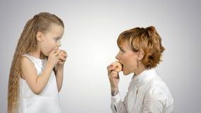 Porträt einer jungen Mutter und ihrer kleinen Tochter, die Äpfel auf weißem Hintergrund essen Lizenzfreie Stockbilder