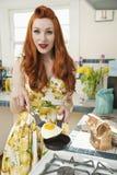 Porträt einer jungen redheaded Frau, die Omelett kocht Lizenzfreies Stockbild
