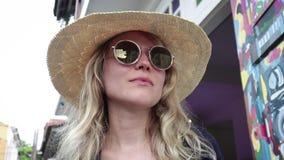 Porträt einer jungen schönen blonden Frau in einem Strohhut und in einer modischen Sonnenbrille stock video