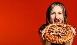 Porträt einer jungen schönen Blondine, die eine köstliche selbst gemachte Kirschtorte hält stockbild