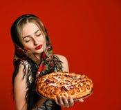 Porträt einer jungen schönen Blondine im Kopftuch, das eine köstliche selbst gemachte Kirschtorte hält lizenzfreie stockfotografie