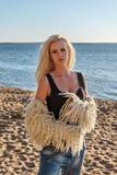 Porträt einer jungen schönen leichten Blondine in den Jeans mit einem schwarzen T-Shirt und einer weißen Pelzjacke auf einem sand lizenzfreies stockfoto