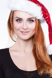 Porträt einer jungen schönen rothaarigen Frau in einem glänzenden Weihnachtshut, spielt sie mit einem flaumigen weißen Pompom Stockbilder