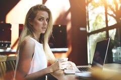Porträt einer jungen schönen Schweden-Frau, die Laptop-Computer verwendet, beim Sitzen in der modernen Kaffeestube, Stockbild