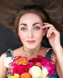 Porträt einer jungen Schönheit, Brunette mit einem Blumenstrauß von Rosen Sie liegt auf dem Boden und hält ihre Hand durch das Ge lizenzfreie stockfotos