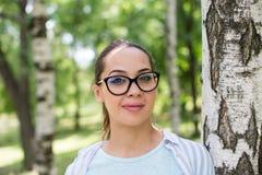 Porträt einer jungen Schönheit in den Gläsern, auf einer grünen Hintergrundsommernatur Lizenzfreie Stockfotografie