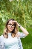 Porträt einer jungen Schönheit in den Gläsern, auf einer grünen Hintergrundsommernatur Stockfotos