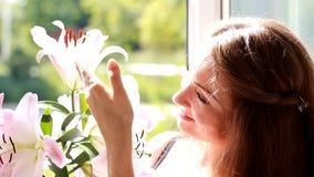 Porträt einer jungen Schönheit mit Lilie Das Mädchen riecht den Geruch von Blumen stock video footage