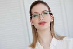 Porträt einer jungen stilvollen Geschäftsfrau in einem weißen Hemd und in den Gläsern lizenzfreie stockbilder