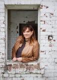 Porträt einer kaukasischen Frau, die Tan Leather Jacket Leaning Out das Fenster eines alten Backsteinbaus trägt Lizenzfreies Stockfoto