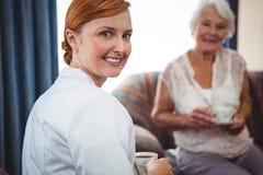 Porträt einer Krankenschwester, die hinter ihr schaut Stockfotografie