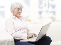 Lächelnde ältere Frau, die an Laptop arbeitet Stockfotografie