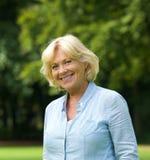 Porträt einer lächelnden älteren Frau draußen Lizenzfreie Stockfotos