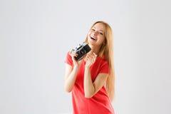 Porträt einer lächelnden attraktiven jungen Frau, die Fotos unter Verwendung der alten Kamera macht Lizenzfreies Stockbild