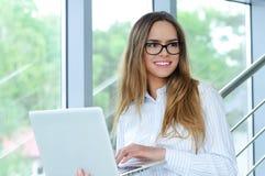 Porträt einer lächelnden erfolgreichen Geschäftsfrau mit Computer stockbilder