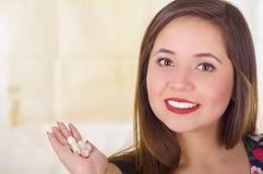 Porträt einer lächelnden Frau, die in ihrer Hand eine vaginale Tablette der weichen Gelatine oder ein Zäpfchen, Behandlung von Kr Stockfoto