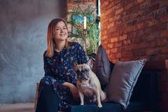 Porträt einer lächelnden Frau, die mit einem netten Pug in ein Raum wi sitzt Lizenzfreies Stockfoto