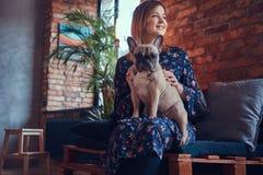 Porträt einer lächelnden Frau, die mit einem netten Pug in ein Raum wi sitzt Lizenzfreies Stockbild