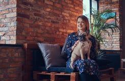 Porträt einer lächelnden Frau, die mit einem netten Pug in ein Raum wi sitzt Stockfotos