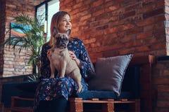 Porträt einer lächelnden Frau, die mit einem netten Pug in ein Raum wi sitzt Stockbilder