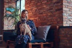 Porträt einer lächelnden Frau, die mit einem netten Pug in ein Raum wi sitzt Lizenzfreie Stockfotografie