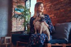 Porträt einer lächelnden Frau, die mit einem netten Pug in ein Raum wi sitzt Lizenzfreie Stockfotos