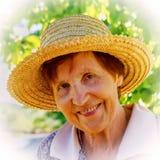 Porträt einer lächelnden Frau in einem Strohhut Stockfotografie