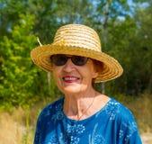 Porträt einer lächelnden Frau in einem Strohhut und in der Sonnenbrille Stockbild